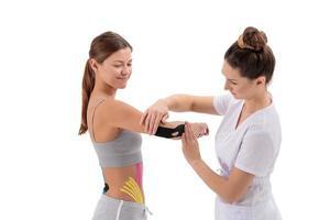 fisioterapista che applica nastro kinesio sul braccio della paziente. kinesiologia, terapia fisica, concetto di riabilitazione. trattamento del gomito del tennista o del golfista. foto