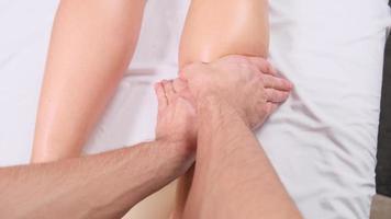 estremo primo piano dell'osteopata che applica pressione con il pollice sul muscolo del polpaccio femminile. foto