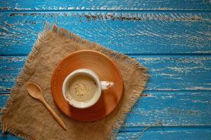 tazza di caffè caldo al mattino su un tavolo di legno rurale blu foto