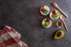 bicchiere di ciliegia e avocado affettati in yogurt su fondo in legno foto