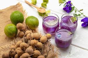 bicchiere di succo di limone, fiori di pisello e longan su tavolo di legno bianco foto