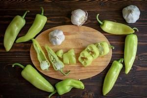 peperoncini piccanti verdi e peperoncino affettato con aglio su fondo di legno foto
