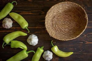 peperoncini piccanti verdi e aglio su fondo di legno foto