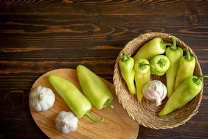 peperoncini piccanti verdi e aglio nel cestello su sfondo di legno foto
