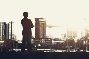 silhouette di uomo d'affari in piedi sul tetto guardando il paesaggio urbano al tramonto. copyspace per il testo. foto