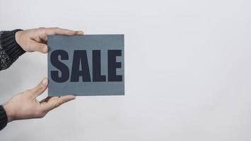 mani dell'uomo che tengono un cartello che dice vendita foto