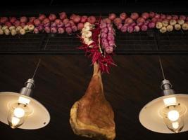 tradizionale prosciutto spagnolo jamon, appeso accanto a peperoncino e cipolle foto