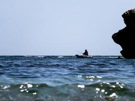 pescatore in un gommone in mare contro il cielo blu foto