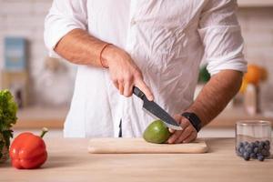 le mani dello chef che tagliano l'avocado con l'aiuto di un coltello su una superficie bianca foto