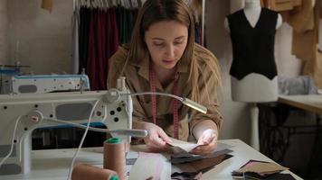 primo piano di una stilista su misura che sceglie un modello in pelle colorata che passa attraverso campioni vicino alla macchina da cucire presso lo studio di design foto