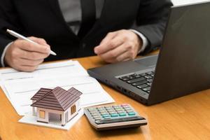 funzionario di banca calcola i tassi di interesse mutuo per la casa mensilmente per l'acquirente foto