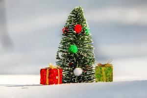albero di natale sulla neve con confezione regalo rossa e verde foto