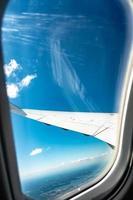 guardando sopra l'ala di un aereo in volo foto