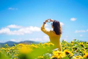 felice estate spensierata donna nel campo di girasoli in primavera. mani di donna asiatica multirazziale allegra che formano una forma di cuore sul campo di girasoli foto