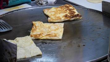 produzione di roti, roti fritti in padella, cibo di strada tradizionale indiano foto