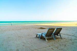 sedia a sdraio vuota sulla sabbia con lo sfondo del mare oceano foto