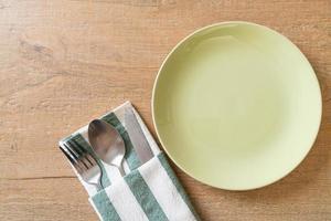 piatto vuoto o piatto con coltello, forchetta e cucchiaio su sfondo di piastrelle di legno foto
