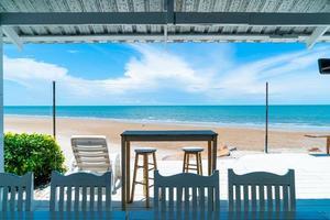 bar e sedia in legno con spiaggia oceano mare e sfondo azzurro del cielo foto