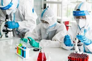 scienziati in dispositivi di protezione individuale o dpi che fanno ricerca e sperimentano per trovare farmaci per trattare l'infezione da covid-19 o coronavirus in laboratorio foto