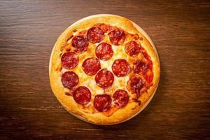 pizza ai peperoni su vassoio di legno - stile alimentare italiano foto