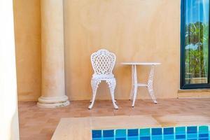 sedia bianca vuota e tavolo a lato della piscina foto