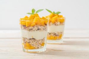 yogurt al mango fresco con muesli in vetro - stile di cibo sano foto