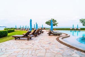 piscine per sedie o piscine per lettini e ombrelloni intorno alla piscina con sfondo di spiaggia di mare foto