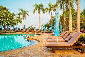 sedie piscine e ombrelloni intorno alla piscina con palme da cocco - vacanze e concetto di vacanza vacation foto