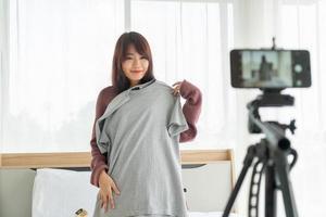 bella donna asiatica blogger che mostra vestiti sulla fotocamera per registrare video vlog in streaming live nel suo negozio - influencer online sul concetto di social media foto