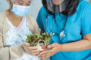 asiatico anziano o anziana signora anziana paziente che mangia colazione vegetale cibo sano con speranza e felice mentre è seduto e affamato sul letto in ospedale. foto