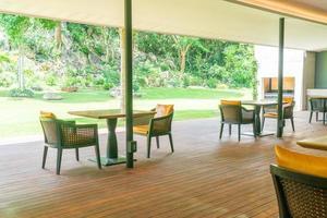 sedia da giardino e tavolo sul balcone con sfondo giardino foto