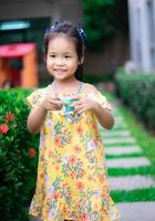 il ritratto della piccola ragazza asiatica sveglia si diverte con la macchina fotografica del giocattolo nel parco foto