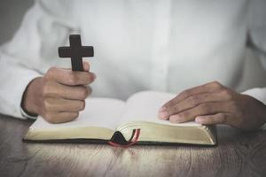 la donna tiene la croce e prega con le sue scritture sulla tavola. foto