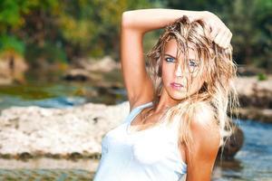 bella donna bionda in stile selvaggio selvaggio con gli occhi azzurri con i capelli bagnati arruffati foto