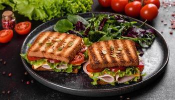 delizioso panino con crostini, prosciutto, lattuga e pomodori foto