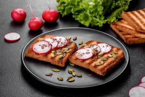 delizioso panino croccante con pane tostato, ravanello, semi di zucca e semi di lino foto