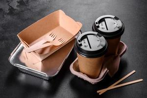 piatti usa e getta realizzati in cartone marrone ecologico su sfondo scuro foto