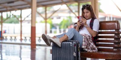 giovane donna che usa il suo smartphone mentre aspetta il treno foto