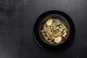 zuppa calda deliziosa fresca con pasta e uova di quaglia in un piatto nero foto