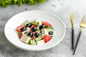 deliziosa insalata greca fresca con pomodoro, cetriolo, cipolle e olive con olio d'oliva foto