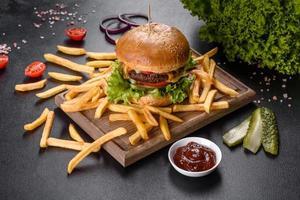delizioso hamburger fresco con cotoletta di manzo, pomodori e lattuga con patatine fritte foto