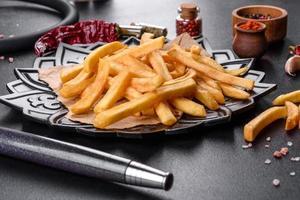 gustose patatine fritte con sale e spezie su sfondo scuro foto