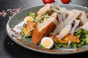 deliziosa insalata caesar fresca con carne di pollo, pangrattato, pomodori e foglie di lattuga foto