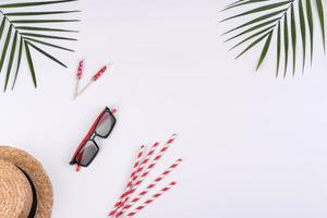 accessori da spiaggia, occhiali e cappello con conchiglie e stelle marine su sfondo colorato foto