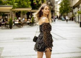 giovane donna bruna capelli lunghi che cammina per strada foto