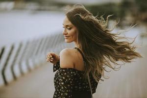 giovane donna bruna capelli lunghi che cammina sulla riva del fiume foto