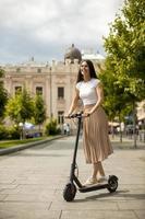giovane donna in sella a uno scooter elettrico su una strada foto