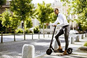 giovane afroamericano utilizzando scooter elettrico su una strada foto