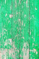 primo piano di una vecchia porta di legno, vernice verde che si staccava dallo sfondo della trama foto