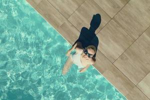 giovane bella ragazza sexy che si gode il nuoto nella piscina privata e si rilassa al sole foto